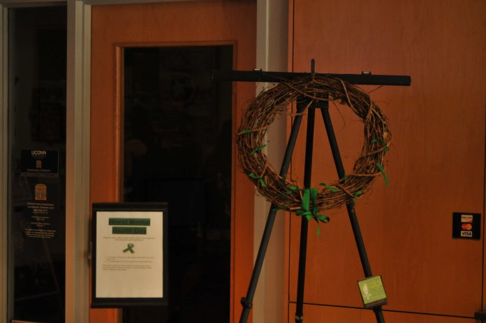 A wreath is placed in the Student Union to raise awareness for people struggling with mental health issues. People are encouraged to add a green ribbon by tying it to the wreath to show their support. (Brandon Barzola/The Daily Campus)