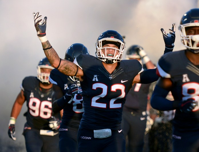 In this Aug. 30 file photo, UConn linebacker Eli Thomas raises his arms to the crowd as his team enters the field for their season-opening game against Central Florida at Rentschler Field. (Stephen Dunn, File/AP)