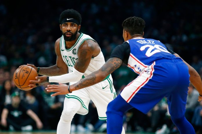 Boston Celtics' Kyrie Irving looks to pass against Philadelphia 76ers' Markelle Fultz (20) during the first half of an NBA basketball game in Boston, Tuesday, Oct 16, 2018. (AP Photo/Michael Dwyer)