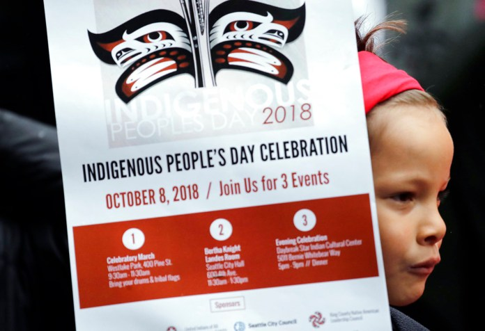 A child holds a poster about Indigenous Peoples Day during a blessing and rally before a march Monday, Oct. 8, 2018, in Seattle. In 2014, the Seattle City Council voted to stop recognizing Columbus Day and instead turned the second Monday in October into a day of recognition of Native American cultures and peoples. (AP Photo/Elaine Thompson)
