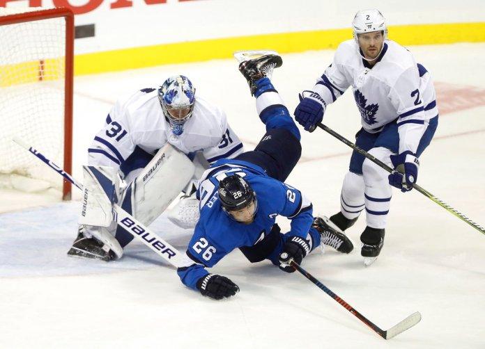 Winnipeg Jets' Blake Wheeler (26) crashes over Toronto Maple Leafs goaltender Frederik Andersen (31) after colliding with Ron Hainsey (2) during first period NHL hockey action in Winnipeg, Manitoba, Wednesday, Oct. 24, 2018. (Trevor Hagan/The Canadian Press via AP)