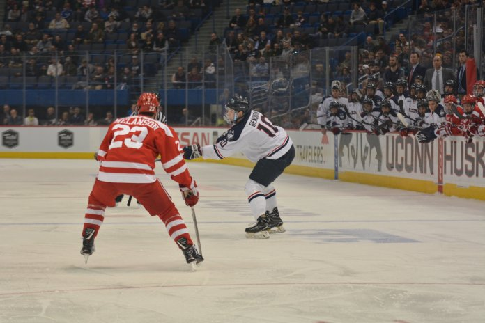 Miles Gendron dishes a pass during a game f against Boston College in a heated game at the XL center on Friday, Feb. 16, 2018. File photo/The Daily Campus