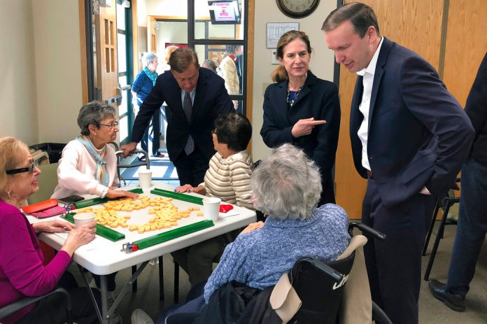 In this Oct. 18, 2018 photo, U.S. Sen. Chris Murphy, right, campaigns at a senior center in West Hartford, Conn., with the Democratic ticket for governor, Greenwich businessman Ned Lamont, left rear, and his running mate Susan Bysiewicz, center. Murphy is playing an out-sized role in Connecticut's elections this year, transferring $320,000 to the state Democratic party, helping with volunteer training, campaigning with candidates and helping to recruit a congressional candidate. (AP Photo/Susan Haigh)