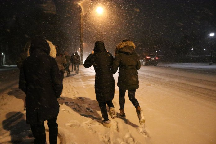 Snow falls on the UConn campus Thursday night with mixed reactions from students. (Photo by Maggie Chafouleas/The Daily Campus)