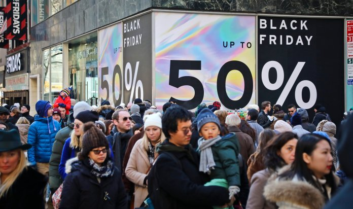 Crowds walk past a large store sign displaying a Black Friday discount in midtown Manhattan, Friday, Nov. 23, 2018, in New York.  (AP Photo/Bebeto Matthews)