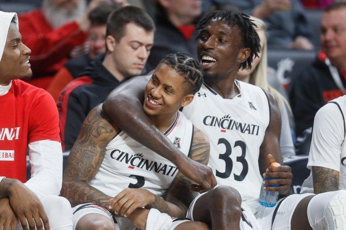 Cincinnati's Justin Jenifer (3) and Nysier Brooks (33) celebrate on the bench during a game against Western Michigan on Monday, Nov. 19 in Cincinnati. (John Minchillo/AP)