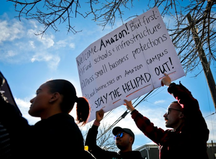 Protesters hold up anti-Amazon signs during a coalition rally and press conference opposing Amazon headquarters getting subsidies to locate in the New York neighborhood of Long Island City, Queens, Wednesday Nov. 14, 2018, in New York. (AP Photo/Bebeto Matthews)
