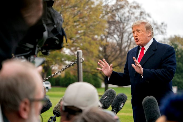 In this Nov. 26, 2018, photo, President Donald Trump speaks to members of the media before boarding Marine One on the South Lawn of the White House in Washington. Trump has moved steadily to dismantle Obama administration efforts to rein in coal, oil and gas emissions, even as warnings grow _ from his own administration and others _ about the devastating impact of climate change on the U.S. economy as well as the earth. Trump has dismissed his administration's warnings about the impact of climate change, including a forecast, released Friday, that it could lead to economic losses of hundreds of billions of dollars by the end of the century. (AP Photo/Andrew Harnik)