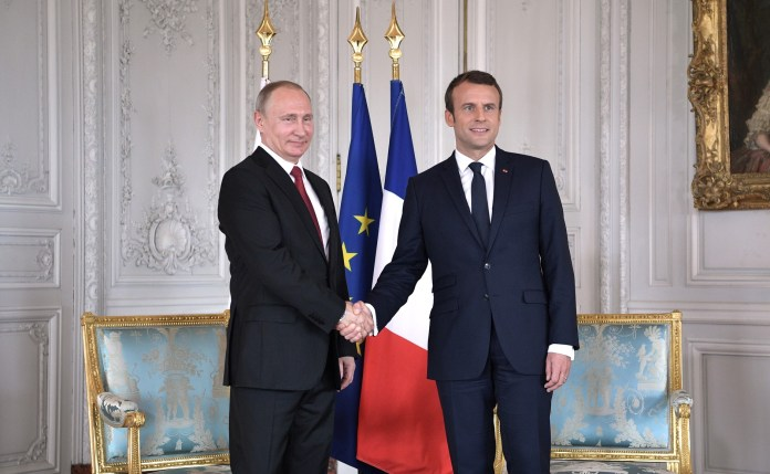 Russian President Vladimir Putin (left) and French President Emmanuel Macron shake hands and pose for a picture in a meeting on May 29, 2017. (Photo courtesy of WikiMedia Commons)