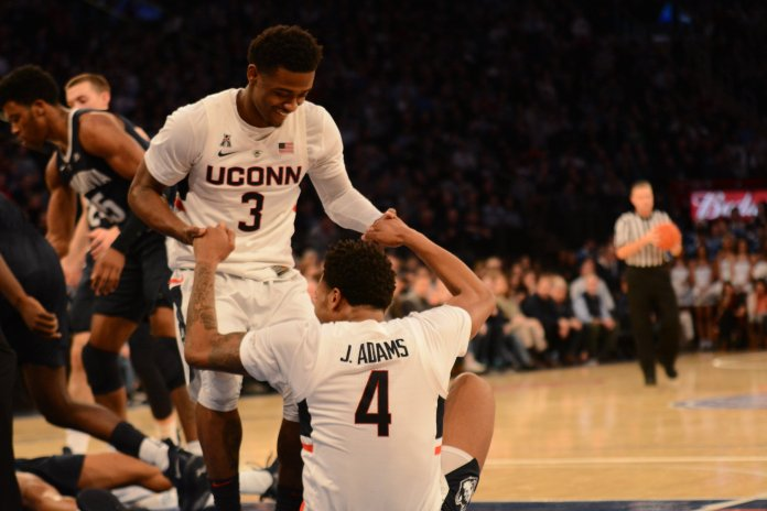Alterique Gilbert helps up teammate Jalen Adams during UConn's 81-58 loss to Villanova at Madison Square Garden on Saturday, Dec. 22, 2018. Gilbert was one of two Huskies to score in double digits with 14 points. (Eric Wang/The Daily Campus)
