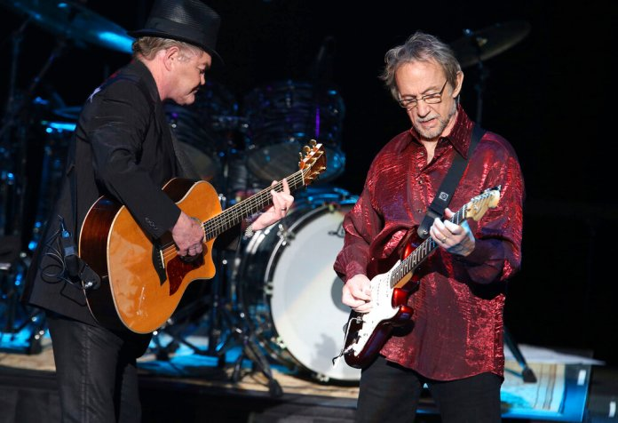 In this June 30, 2016 photo, Micky Dolenz, left, and Peter Tork of The Monkees perform at the Joint at the Hard Rock Hotel and Casino in Tulsa, Okla. Tork, who rocketed to teen idol fame in 1965 playing the lovably clueless bass guitarist in the made-for-television rock band The Monkees, died Thursday, Feb. 21, 2019, of complications related to cancer, according to his son Ivan Iannoli. He was 77. (Tom Gilbert/Tulsa World via AP)