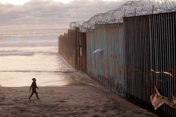 In this Jan. 9, 2019 file photo, a woman walks on the beach next to the border wall topped with razor wire in Tijuana, Mexico. A group of former U.S. national security officials is set to release a statement on Monday, Feb. 25, arguing that there is no justification for President Donald Trump to use a national emergency declaration to fund a wall along the U.S.-Mexico border. (AP Photo/Gregory Bull, File)