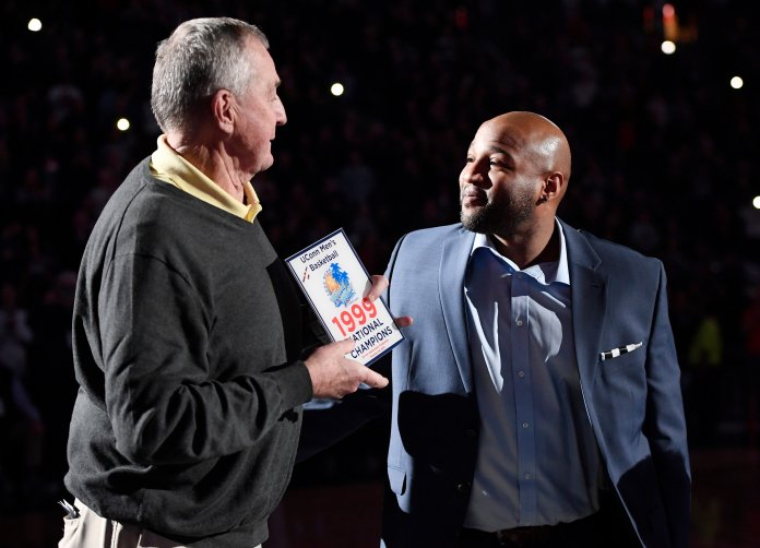 Former Connecticut head coach Jim Calhoun, left, presents former player Khalid El-Amin with a plaque during a special halftime ceremony honoring the 1999 national championship team during an NCAA college basketball game between Connecticut and Cincinnati, Sunday, Feb. 24, 2019, in Hartford, Conn. (AP Photo/Jessica Hill)
