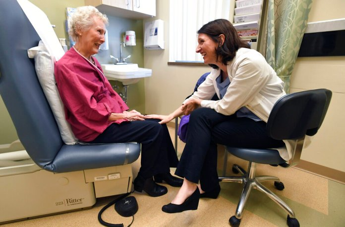 In this Monday, March 4, 2019 photo, Dr. Allison Magnuson, left, speaks with patient Nancy Simpson at the Pluta Cancer Center in Rochester, N.Y. (AP Photo/Adrian Kraus)