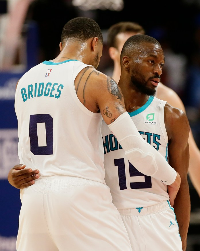 Charlotte Hornets forward Miles Bridges (0) hugs guard Kemba Walker (15) late in the fourth quarter of a win over the Detroit Pistons in an NBA basketball game Sunday, April 7, 2019, in Detroit. (AP Photo/Duane Burleson)