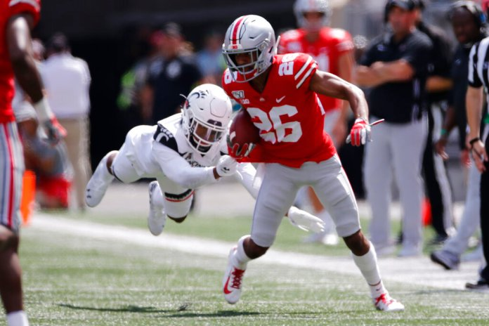 Ohio State running back Jaelen Gill, right, tries to get away from Cincinnati defensive back Cam Jefferies during the second half of an NCAA college football game.   Photo by Jay LaPrete/Associated Press