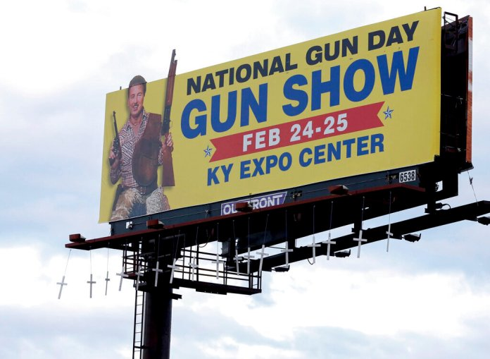 Seventeen crosses bearing the names and ages of those killed in last month's shooting at Marjory Stoneman Douglas High School in Parkland, Fla., were hung overnight from a Louisville billboard that advertises a local gun show.  Scott Utterback / Courier Journal