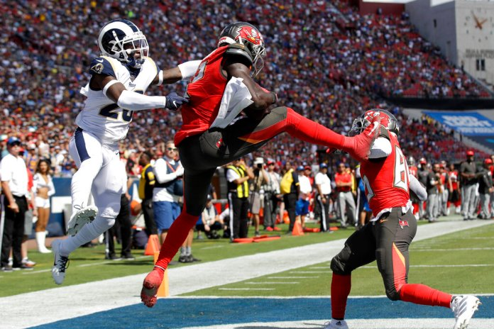 Tampa Bay Buccaneers wide receiver Chris Godwin, middle, scores ahead of Los Angeles Rams defensive back Nickell Robey-Coleman, left, during the first of an NFL football game Sunday.   Photo by Marcio Jose Sanchez/AP