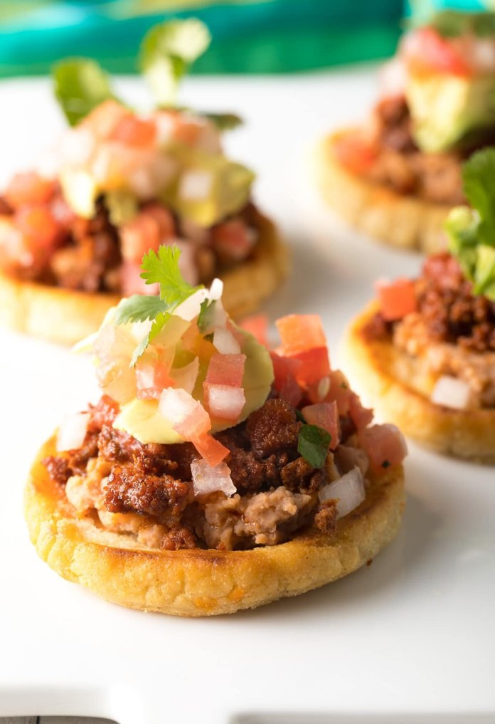 Sopes are a traditional Mexican dish that is similar to tortillas topped with beans, cheese, meat and veggies. This Mexican dish is easy to make and packed with flavors.  Image courtesy of    aspicyperspective.com