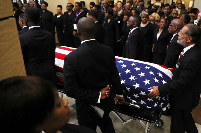 Mourners watch as the flag-draped casket of Rep. Elijah Cummings, D-Md., is brought out of the New Psalmist Baptist Church in Baltimore, Md., after his funeral service on Friday, Oct. 25, 2019.  Photo by Chip Somodevilla/Pool via AP. Thumbnail photo by Chip Somodevilla/Pool via AP.