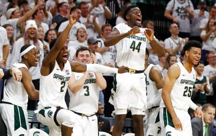 From left, Michigan State guards Cassius Winston (5), Rocket Watts Jr. (2), Foster Loyer (3), and forwards Gabe Brown (44) and Malik Hall (25) react on the bench as guard Steven Izzo scores his first point on a free throw during the second half of an NCAA college exhibition basketball game against Albion, Tuesday, Oct. 29, 2019, in East Lansing, Mich.  Photo by Carlos Osorio/AP