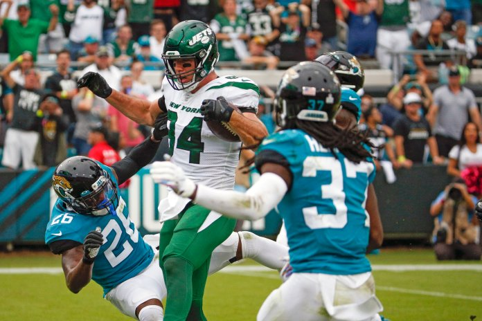 New York Jets tight end Ryan Griffin, center, runs into the end zone for a touchdown between Jacksonville Jaguars defensive back Jarrod Wilson (26) and cornerback Tre Herndon (37) during the first half of an NFL football game, Sunday, Oct. 27, 2019, in Jacksonville, Fla. (AP Photo/Stephen B. Morton)
