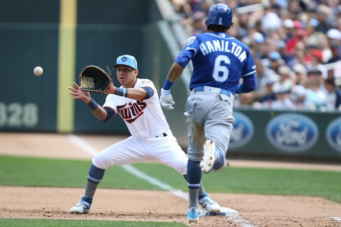 Minnesota Twins' Ehire Adrianza, left, catches the ball at first to get out Kansas City Royals' Billy Hamilton during the fifth inning of a baseball game in Minneapolis.  Photo by Stacy Bengs/AP