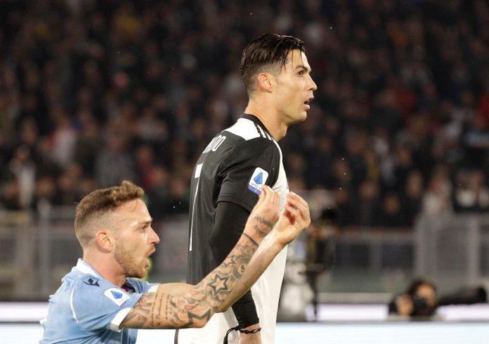 Lazio's Manuel Lazzari, left, reacts as Juventus' Cristiano Ronaldo looks on during the Italian Serie A soccer match between Lazio and Juventus at Rome's Olympic stadium, in Rome, Italy, Saturday, Dec. 7, 2019. (AP Photo/Gregorio Borgia)