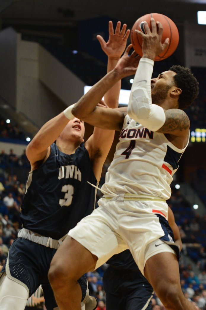 In this Saturday, Nov. 24, 2019 photo Jalen Adams rises up and draws contact against New Hampshire's Nick Guadarrama. The Huskies will play against the New Hampshire Wildcats at 1 p.m. at the XL Center.  Photo by Eric Wang / The Daily Campus