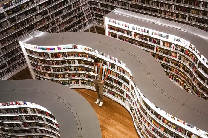 man-standing-inside-library-while-reading-book-3494806.jpg