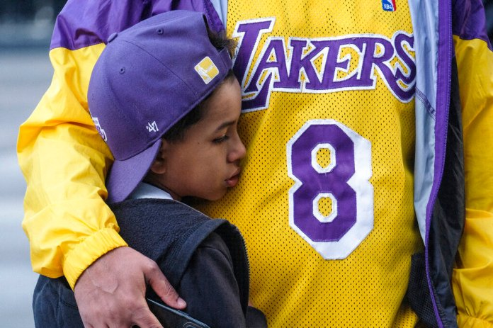 Eric Mascarenhas comforts his son Nicolas at a memorial for Kobe Bryant near Staples Center Monday, in Los Angeles. Eric, right, is wearing a vinatge Bryant jersey, with his old No. 8.  Photo courtesy of Ringo H.W. Chiu/AP Photo