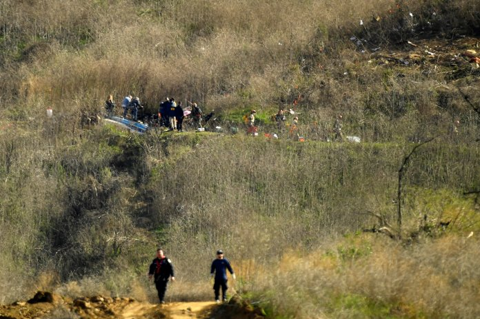 Investigators work the scene of a helicopter crash that killed several people including former NBA basketball player Kobe Bryant, his 13-year-old daughter, Gianna, Calif. (AP Photo/Mark J. Terrill)