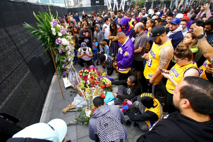 Fans of Kobe Bryant mourn at a memorial to him in front of Staples Center, home of the Los Angeles Lakers, after word of the Lakers star's death in a helicopter crash, in downtown Los Angeles Sunday.  Photo courtesy of Matt Martman/AP Photo