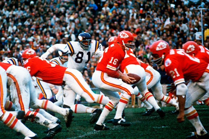 In this Jan. 11, 1970, file photo, Kansas City Chiefs quarterback Len Dawson (16) turns around to hand the ball off to running back Mike Garrett (21) during the Super Bowl IV football game in New Orleans. As the Chiefs prepare to play the San Francisco 49ers on Sunday, Feb. 2, 2020, many members of the 1970 team never lived to see the the Chiefs return to the championship game, and many others are in failing health. (AP Photo/File)