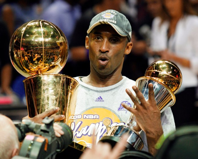 Los Angeles Lakers' Kobe Bryant holds the Larry O'Brien championship trophy and finals MVP trophy after the Lakers defeated the Orlando Magic 99-86 in Game 5 of the 2009-10 NBA basketball finals in Orlando, Fla. Bryant, the 18-time NBA All-Star who won five championships and became one of the greatest basketball players of his generation during a 20-year career with the Los Angeles Lakers, died in a helicopter crash Sunday. He was 41.  Photo courtesy of David J. Phillip/AP Photo