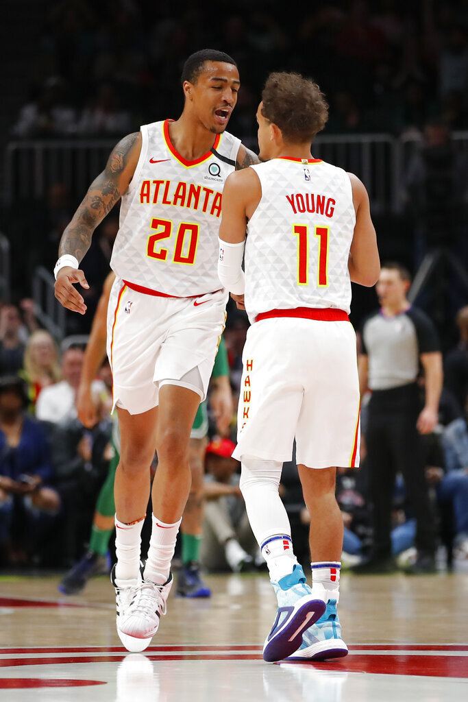Atlanta Hawks forward John Collins reacts with guard Trae Young in the first half of a game against the Boston Celtics on Monday in Atlanta. The Hawks added center Clint Capela Wednesday in a blockbuster trade.  Photo courtesy of Todd Kirkland/AP Photo