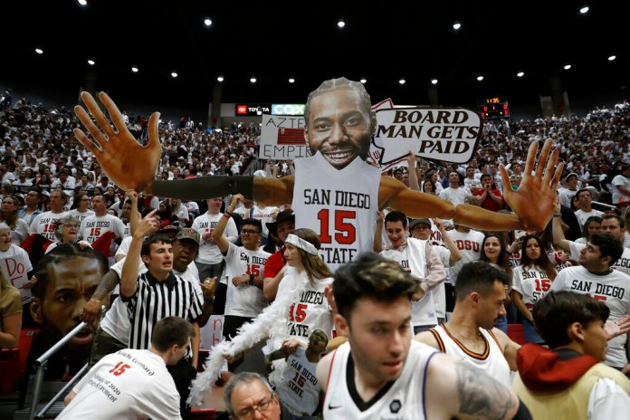 San Diego State fans hold up an image of former San Diego State forward Kawhi Leonard, now with the Los Angeles Clippers, before basketball game against Utah State Saturday in San Diego. San Diego State is undefeated on the year.  Photo courtesy of Gregory Bull/AP Photo