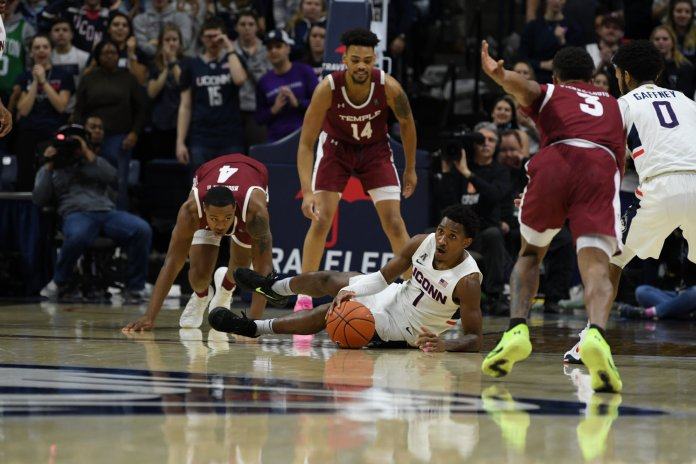 The UConn men's basketball team's Christian Vital dives for a loose ball in a win against Temple. UConn dropped a game versus SMU 79-75.  Photo by Brandon Barzola/The Daily Campus