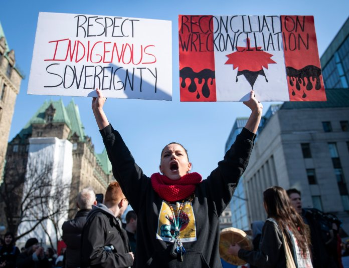 A woman holds signs as demonstrators block vehicular traffic along Wellington Street in Ottawa at a rally in solidarity with Wet'suwet'en hereditary chiefs opposed to the Costal GasLink Pipeline, on Monday, Feb. 24, 2020.  Photo courtesy of Justin Tang / The Canadian Press via AP