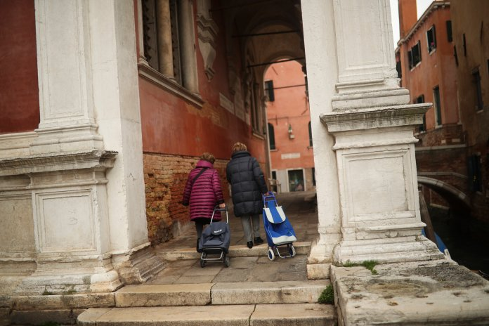 Two local women pull their trolleys in their way to the supermarket in Venice, Monday, March 2, 2020. The coronavirus outbreak in northern Italy has so overwhelmed the public health system that officials are taking extraordinary measures to care for the sick, seeking to bring doctors out of retirement and accelerate graduation dates for nursing students. (AP Photo/Francisco Seco)