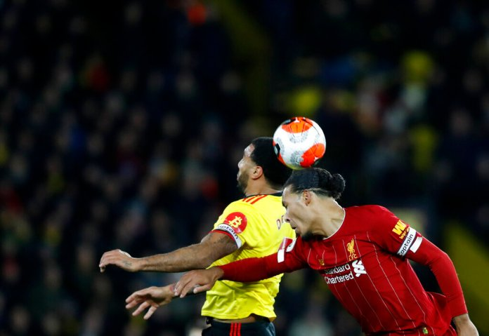 Liverpool's Virgil van Dijk, right, jumps for the ball with Watford's Troy Deeney during the English Premier League soccer match between Watford and Liverpool at Vicarage Road stadium, in Watford, England, Saturday, Feb. 29, 2020.  Photo by Alastair Grant/AP
