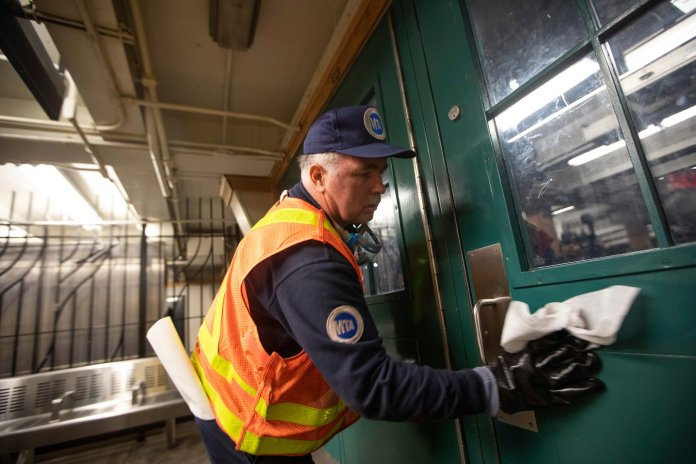 Metropolitan Transportation Authority worker Duane Clark works to sanitize surfaces at the Avenue X subway station, Tuesday, March 3, 2020, in the Brooklyn borough of New York. The MTA is stepping up efforts to sanitize cars and stations as fears mount over the coronavirus.  Photo courtesy of Kevin Hagen / AP Photo.