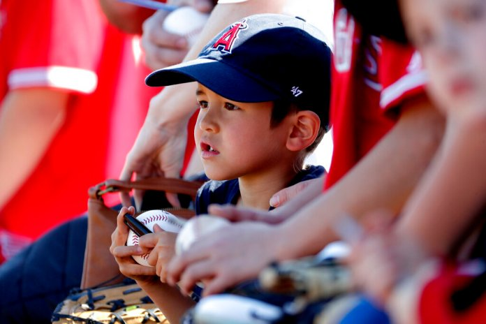 A Los Angeles Angels fan waits for an autograph prior to a spring training baseball game against the Seattle Mariners Wednesday.  Photo courtesy of Matt York/AP