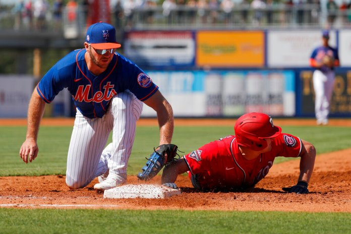 Washington Nationals' Andrew Stevenson, right, dives safely back to first ahead of the tag from New York Mets first baseman Pete Alonso during the second inning of a spring training baseball game Sunday.  Photo courtesy of Jeff Roberson/AP