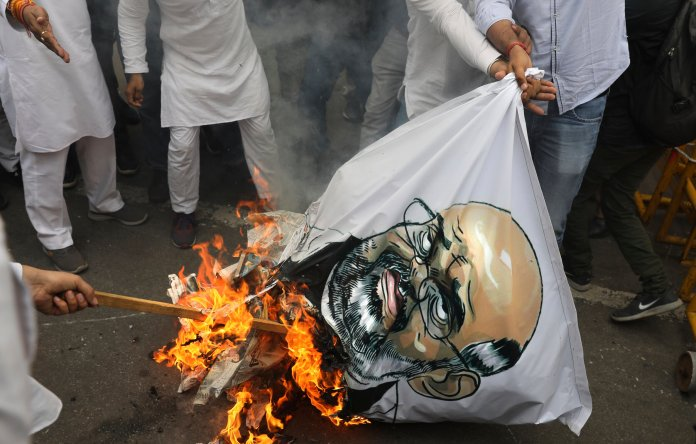 Congress party workers burn an effigy of Indian Home Minister Amit Shah as they protest against last week's deadly communal riots in New Delhi, India, Monday, March 2, 2020. (AP Photo/Manish Swarup)
