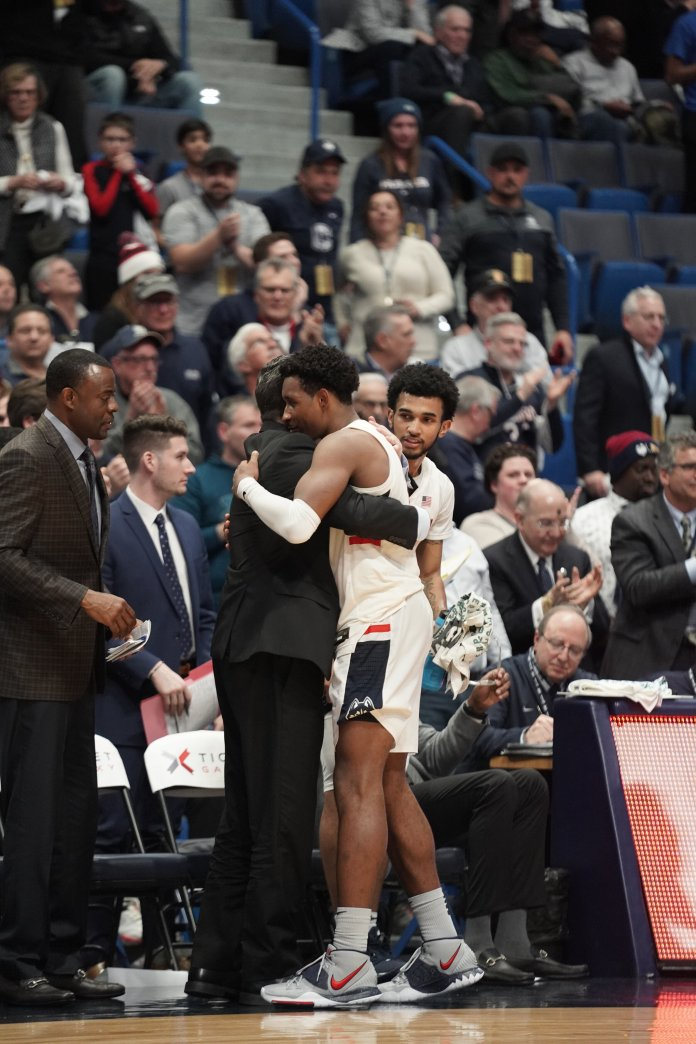 UConn's Christian Vital hugs assistant coach Tom Moore during their win over UCF.  Photo by Eric Wang/The Daily Campus