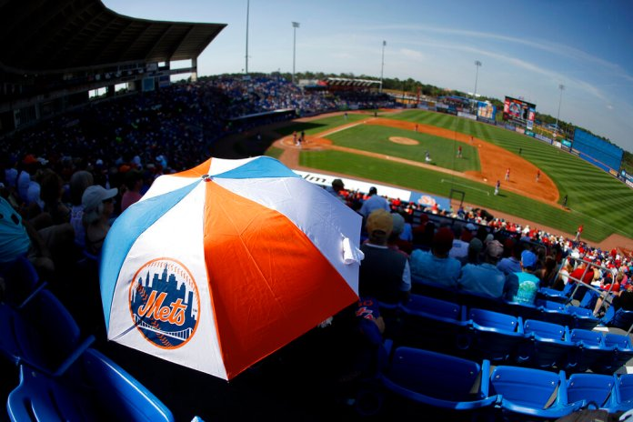 Michelle Alonso, mother of New York Mets first baseman Pete Alonso, hides from the sun under an umbrella during the fifth inning of a spring training baseball game against the St. Louis Cardinals, Wednesday.  Photo courtesy of Julio Cortez/AP