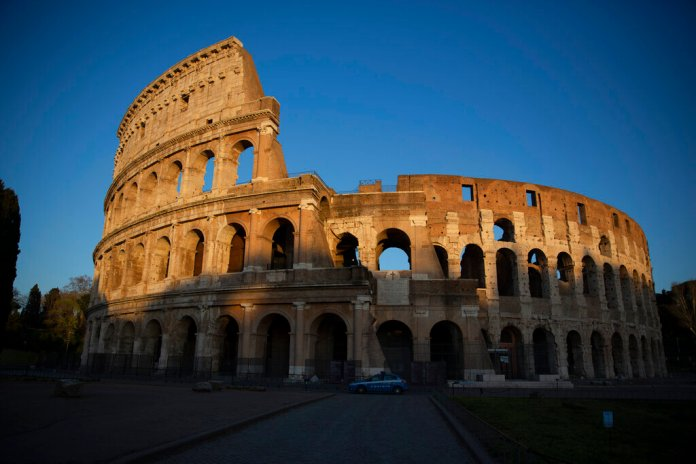 A police car patrols Rome's Colosseum at dusk, Monday, March 23, 2020. For most people, the new coronavirus causes only mild or moderate symptoms. For some it can cause more severe illness, especially in older adults and people with existing health problems.  Photo by Alessandra Tarantino/AP