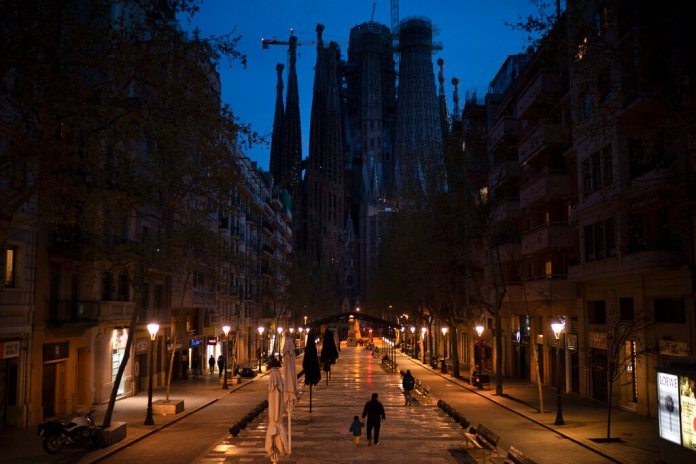 People walk past closed shops and restaurants near the La Sagrada Familia basilica, center, in Barcelona, Spain, March 18, 2020.  Photo by Felipe Dana/AP