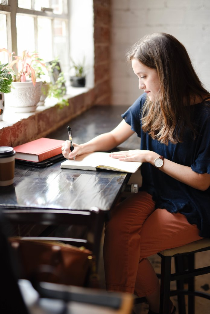 A photo of a woman writing a book. Taking an online masterclass is a great way to learn about the writing process.  Photo by    Hannah Olinger    on    Unsplash